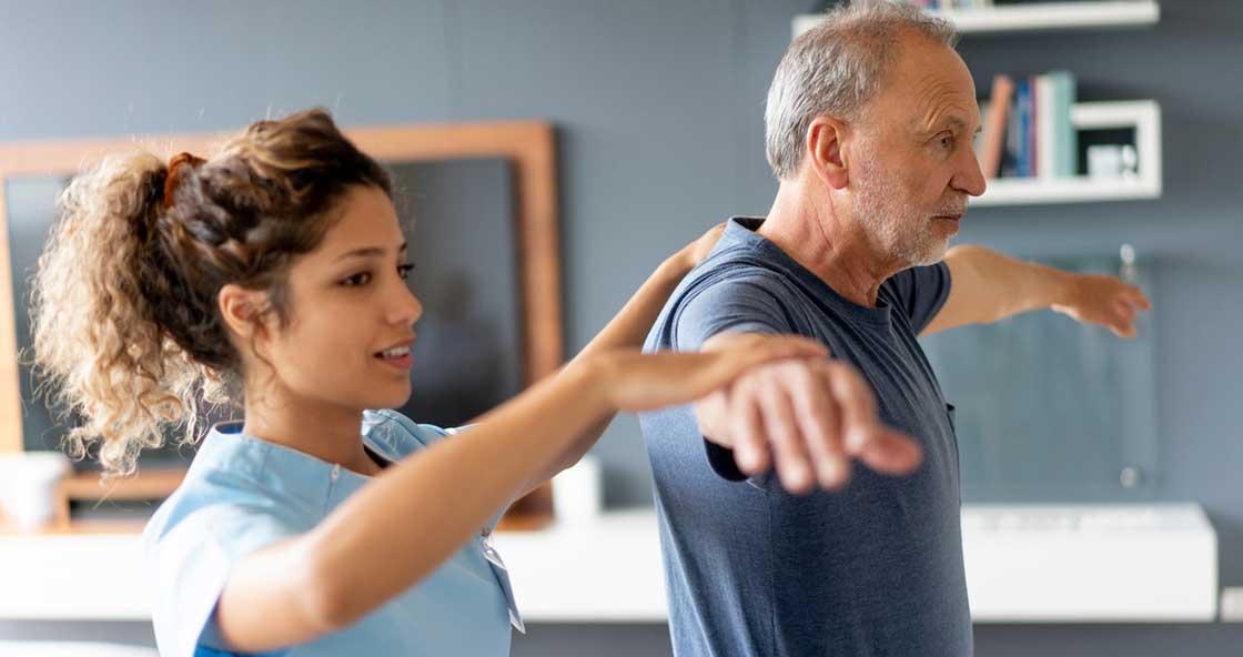fisioterapeuta ayudando a persona mayor en Madrid